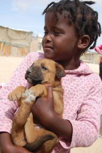 little girl holding her puppy in henties
