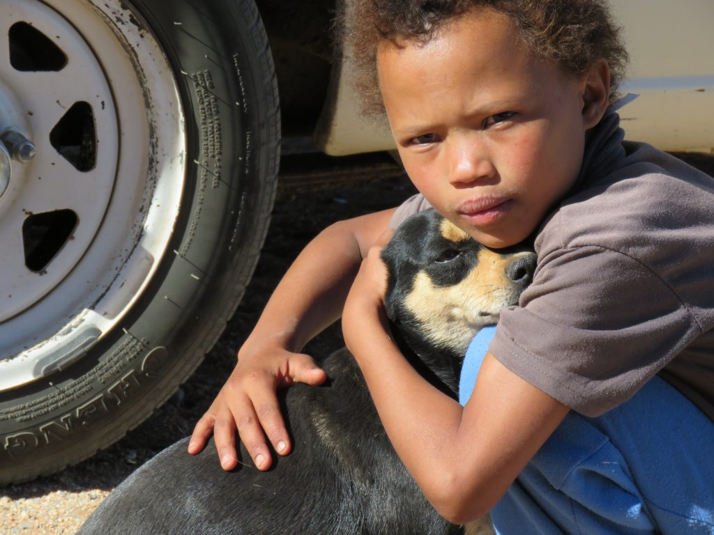 young child is holding his dog close
