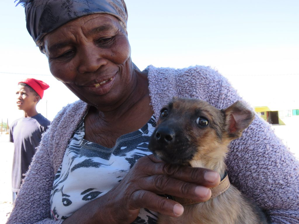 older lady looking at her puppy and smiling