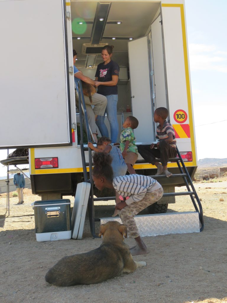 children talking to dr baines of the mobile clinic
