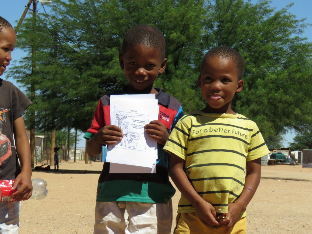 two children with a flyer about pet care
